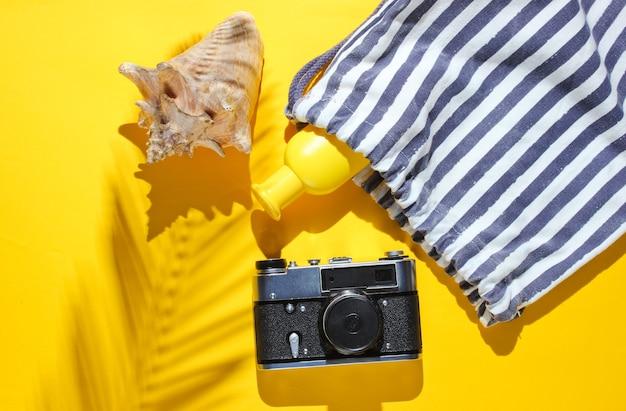 Kreativer urlaub auf meereshintergrund. reisen sie strandzubehör auf gelbem hintergrund mit einem schatten vom tropischen palmblatt. draufsicht