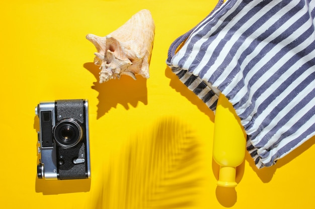 Kreativer urlaub auf meereshintergrund. reisen sie strandzubehör auf gelbem hintergrund mit einem schatten vom tropischen palmblatt.