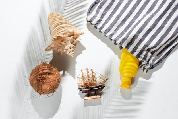 Kreativer urlaub auf meereshintergrund. reisen sie strandzubehör auf weißem hintergrund mit einem schatten vom tropischen palmblatt.