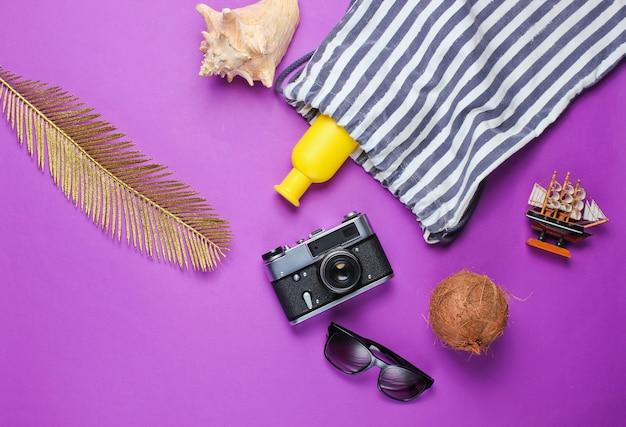 Kreativer urlaub auf meereshintergrund. strandzubehör auf lila hintergrund mit goldenem palmblatt. draufsicht