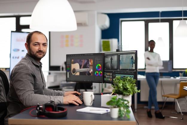 Kreativer videofilmer-künstler-mann, der lächelnd in die kamera schaut