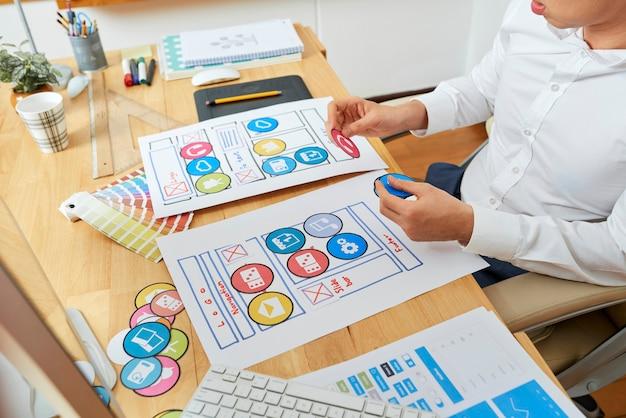 Kreativer webdesigner, der eine mobile anwendung plant und ein vorlagenlayout entwickelt, das papier ausbreitet...