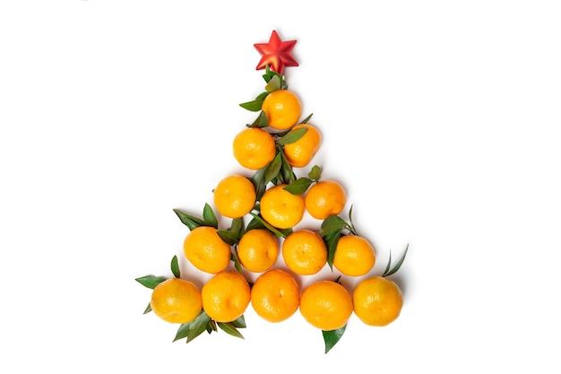 Kreativer weihnachtsbaum aus mandarinen auf einem weißen isolierten hintergrund. roter weihnachtsstern.