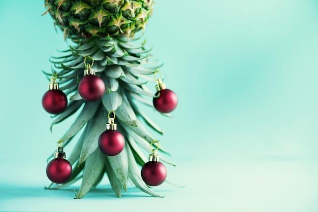 Kreativer weihnachtsbaum gemacht von der ananas und vom roten flitter auf blauem hintergrund
