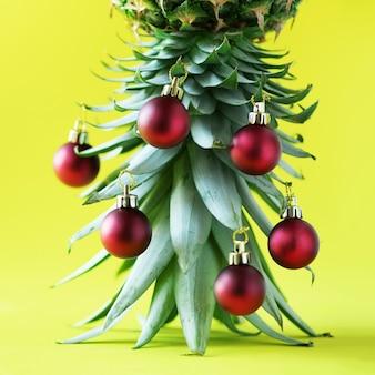 Kreativer weihnachtsbaum gemacht von der ananas und vom roten flitter auf gelbem hintergrund