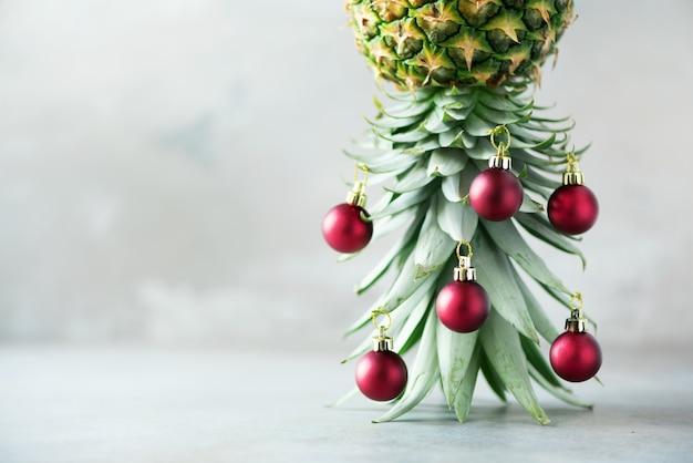 Kreativer weihnachtsbaum gemacht von der ananas und vom roten flitter auf grauem konkretem hintergrund