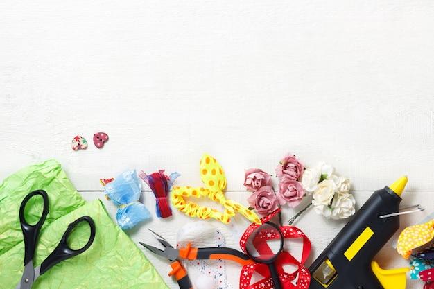 Kreatives arbeitsplatzkonzept: draufsicht auf tabelle mit elementen für scrapbookin und werkzeugen für die dekoration