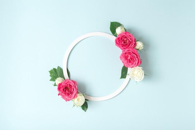 Kreatives arrangement aus weißem rundem rahmen und weißen und rosa rosen auf pastellblauem hintergrund. minimales frühlingsblütenkonzept. platz kopieren.