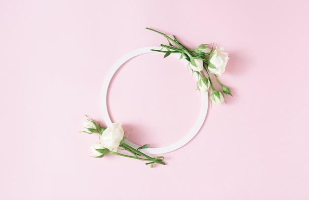 Kreatives arrangement mit weißem rundem rahmen und weißen rosen auf pastellrosa hintergrund. minimales frühlingsblütenkonzept. platz kopieren.