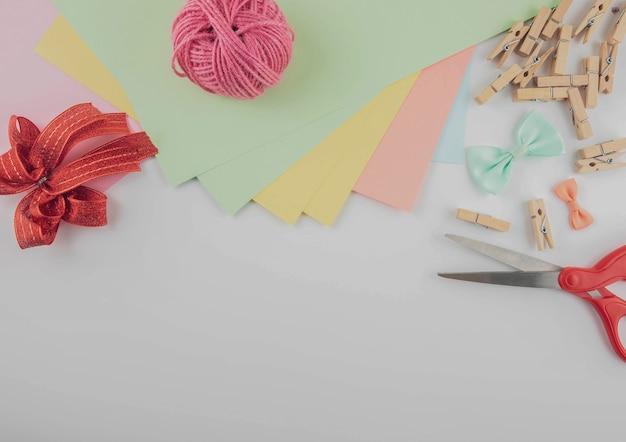 Kreatives bastelbedarf der flachen lage auf weißem schreibtisch mit kopienraum