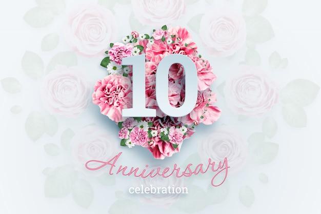 Kreatives beschriften von 10 zahlen und von jahrestagsfeiertext auf rosa blumen, feierereignis, schablone, flieger
