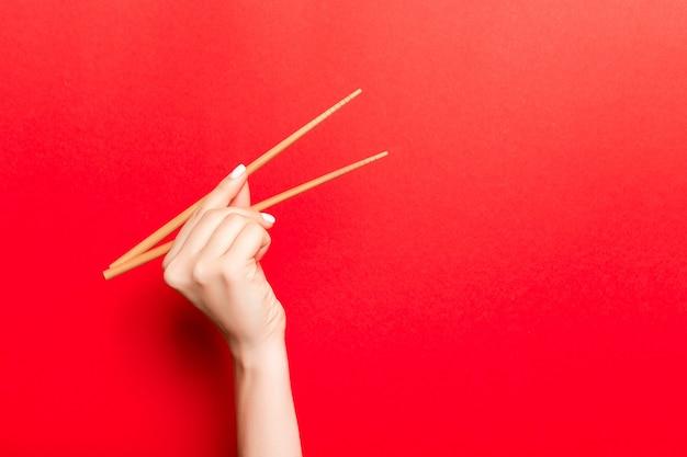 Kreatives bild von hölzernen essstäbchen in der weiblichen hand auf rotem hintergrund. japanisches und chinesisches lebensmittel mit kopienraum