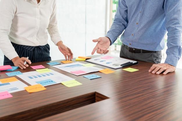 Kreatives brainstorming einer gruppe von geschäftsleuten verwendet die auswahl von haftnotizen, um ideen zur tischentscheidung auszutauschen. auswählen eines konzepts für die entwicklung eines plans im geschäftskonferenzraum.