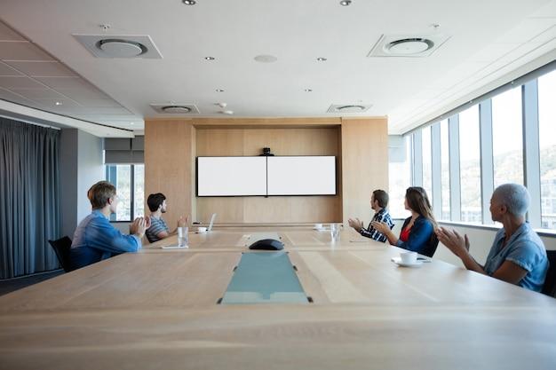 Kreatives business-team, das während der teilnahme an einer telefonkonferenz im büro applaudiert