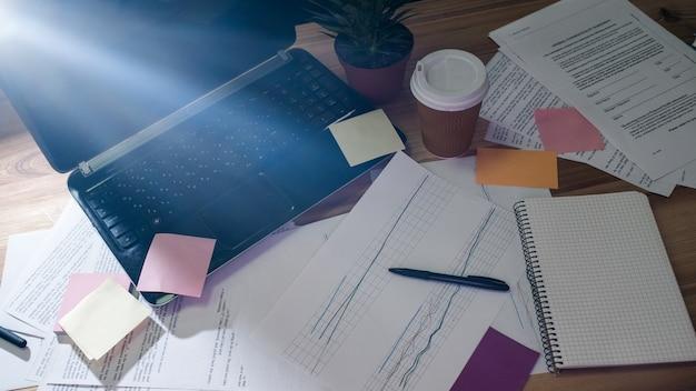 Kreatives chaos im arbeitsprozess. papiere dokumente schreibwaren haftnotizen und notizblock verstreut auf einem schreibtisch-arbeitsplatz
