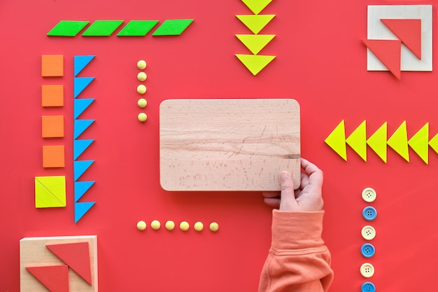 Kreatives design, autismus-welttag, holzbrett in der hand. tangram-puzzle, flach auf rot liegen, textraum