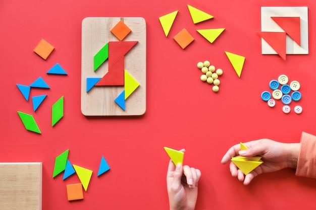 Kreatives design, autismus-welttag, holzbrett in der hand. tangram-puzzle, flach auf rot, piktogramm