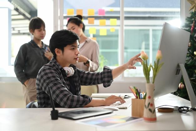 Kreatives designerteam beim brainstorming und einsatz moderner geräte im büro.