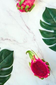Kreatives flaches layout mit frischen organischen rosa drachenfrucht, pitaya oder pitahaya, auf marmortisch