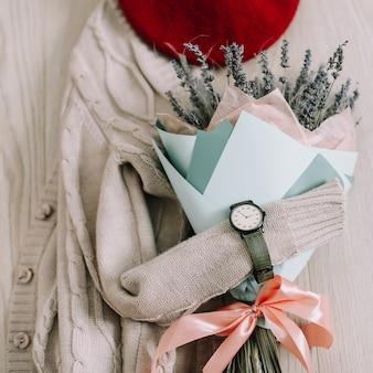 Kreatives flatlay mit blumenstrauß, beigem pullover und damenaccessoires