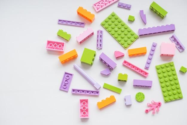 Kreatives gebäude aus hellen erbauerziegeln heraus plastikspielzeugbausteine kreatives gebäude aus hellen erbauerziegeln heraus frühes lernen. entwicklung von spielzeugen. platz zum kopieren. glückliche kindheit.
