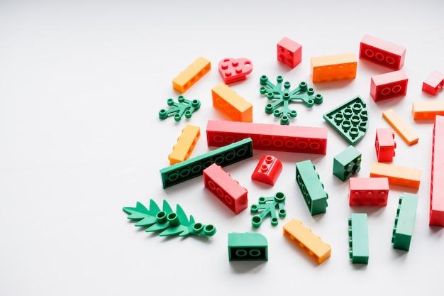 Kreatives gebäude aus hellen erbauerziegeln heraus plastikspielzeugbausteine kreatives gebäude erbauerziegelsteine frühes lernen. entwicklung von spielzeugen. platz zum kopieren. glückliche kindheit.