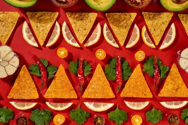 Kreatives geometrisches lebensmittelmuster aus mexikanischen nachos-mais-chips, frischem gemüse, obst, gemüse, chili, knoblauch - zutaten für tomaten-chili-sauce auf rotem grund. flach liegen