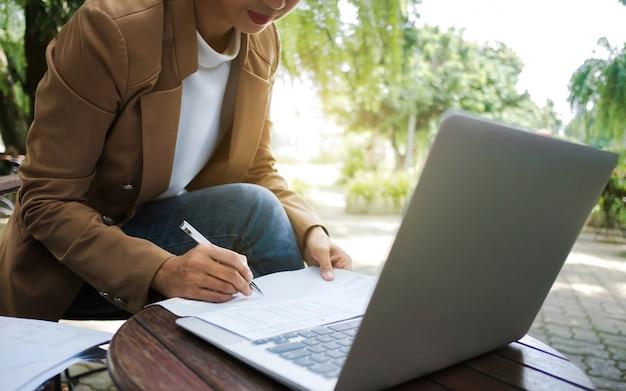 Kreatives geschäft der frau, das laptop an einem im freien mit natur verwendet