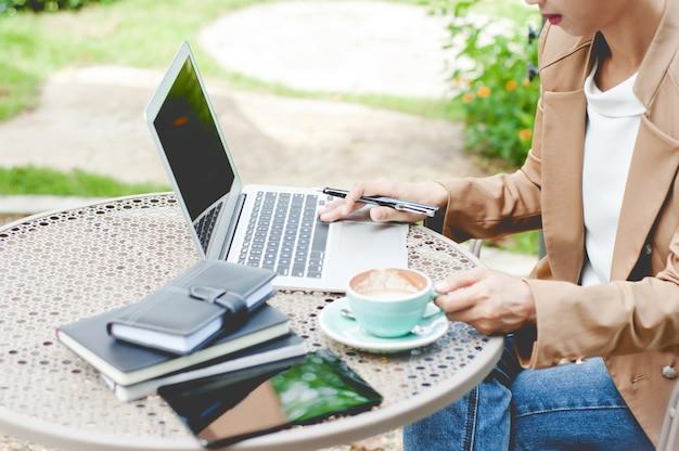 Kreatives geschäft der frau, das mit laptop an einem im freien mit natur arbeitet