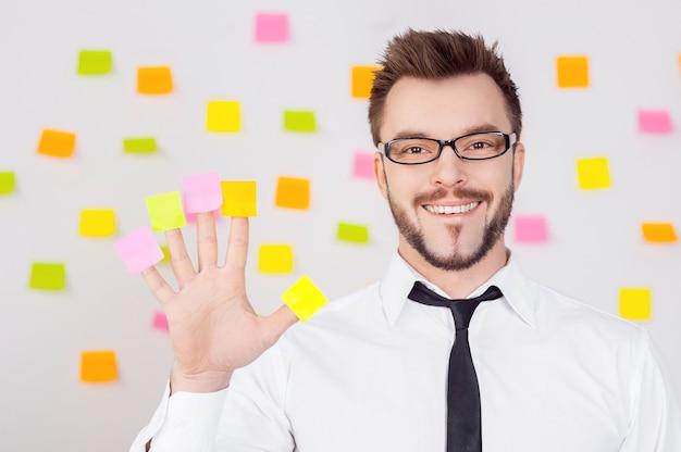 Kreatives geschäft. fröhlicher junger mann in formeller kleidung, der klebenotizen an den fingern hält und lächelt, während er mit vielen klebenotizen an der wand steht