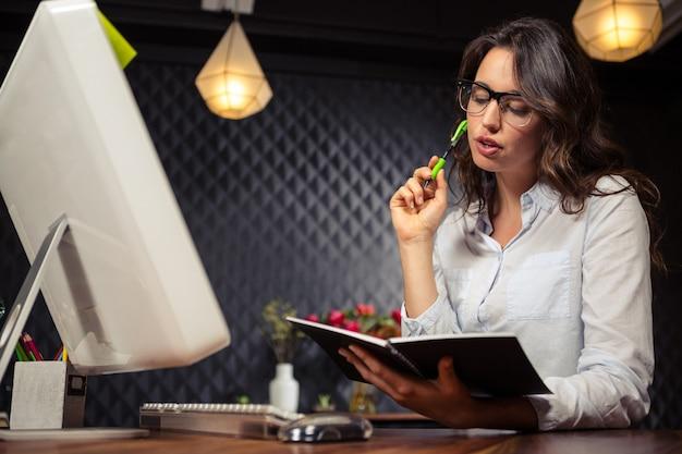 Kreatives geschäftsfrauschreiben auf planer