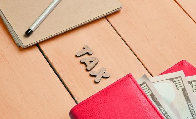 Kreatives geschäftskonzept. notizbuch, bleistift, rote brieftasche mit dollarnoten auf orangefarbenem holztisch mit der wortsteuer der buchstaben