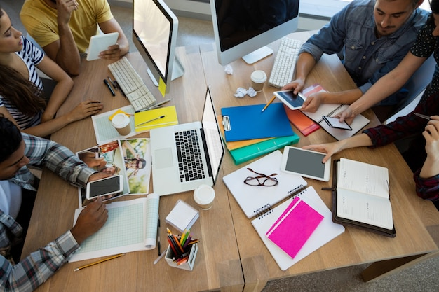 Kreatives geschäftsteam, das an ihrem schreibtisch im büro arbeitet