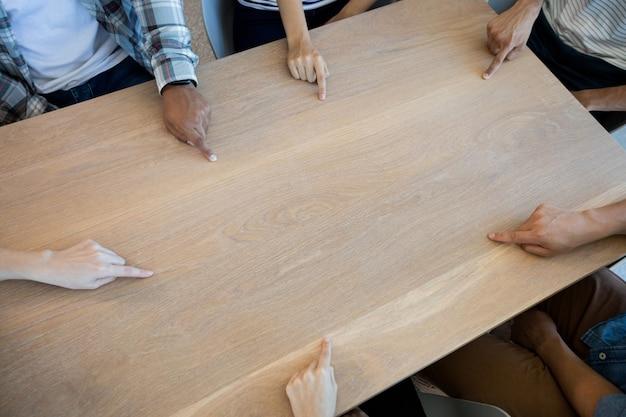 Kreatives geschäftsteam, das auf eine leere kopie auf dem tisch im büro zeigt
