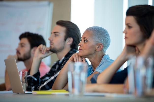 Kreatives geschäftsteam, das beim treffen im konferenzraum im büro zuhört