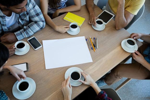 Kreatives geschäftsteam, das besprechung über kaffee im besprechungsraum im büro hat