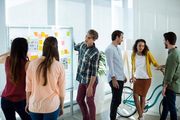 Kreatives geschäftsteam, das haftnotiz betrachtet und im büro diskutiert