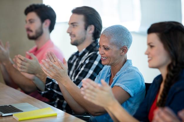 Kreatives geschäftsteam, das im besprechungsraum im büro applaudiert