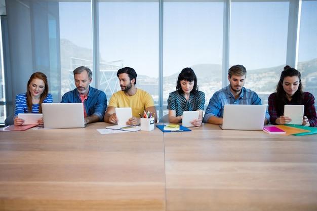 Kreatives geschäftsteam, das in einer reihe sitzt und im büro zusammenarbeitet