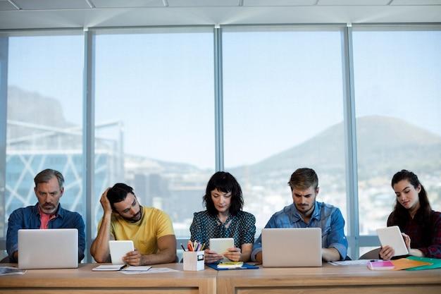 Kreatives geschäftsteam, das in einer reihe sitzt und zusammen auf tisch im büro arbeitet