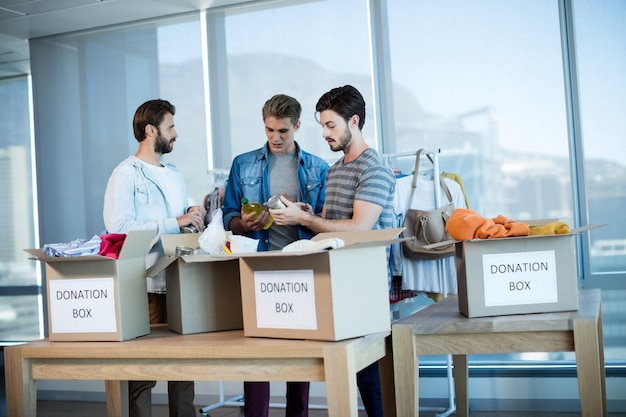 Kreatives geschäftsteam, das kleidung in der spendenbox im büro sortiert