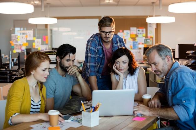 Kreatives geschäftsteam, das über den laptop im büro diskutiert