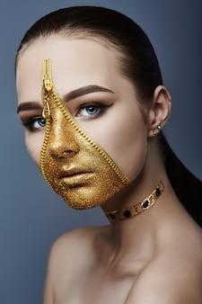 Kreatives grimmiges make-up-gesicht des mädchens goldene farbe reißverschlusskleidung auf der haut. kreative kosmetik der modeschönheit und hautpflege halloween. brünette frau auf dunklem hintergrund, schöne große augen und glatte haut