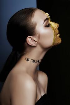 Kreatives grimmiges make-upgesicht der goldenen farbreißverschlusskleidung des mädchens auf haut. kreative kosmetik der modeschönheit und hautpflege halloween. brunettefrau auf dunklem hintergrund, schönen großen augen und glatter haut