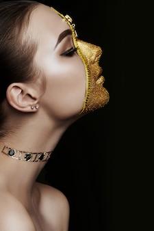Kreatives grimmiges make-upgesicht der goldenen farbreißverschlusskleidung des mädchens auf haut. mode schönheit