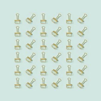 Kreatives grußkartenmuster mit büromaterial, goldenen metallklammern.