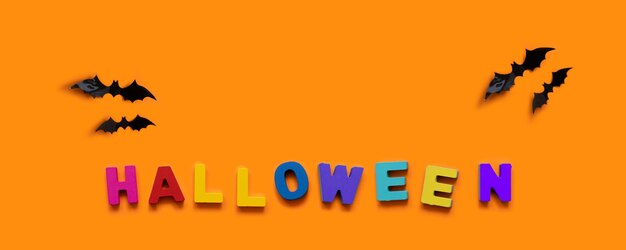 Kreatives herbstkonzept halloweens. schwarze fledermäuse und bunte inschrift