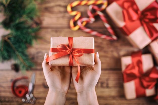 Kreatives hobby. die hände der frau zeigen handgemachtes geschenk des weihnachtsfeiertags im kraftpapier mit band. bilden des bogens an weihnachtsgeschenkbox