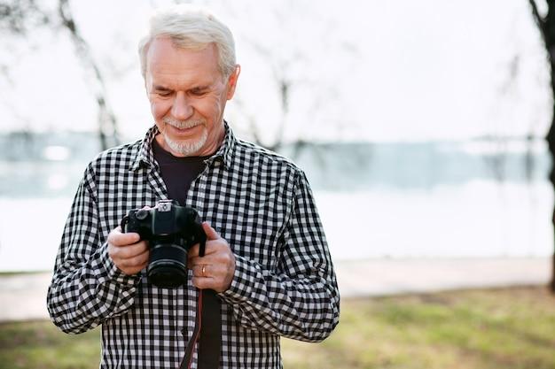Kreatives hobby. glücklicher älterer mann, der auf dem unscharfen hintergrund aufwirft und kamera verwendet