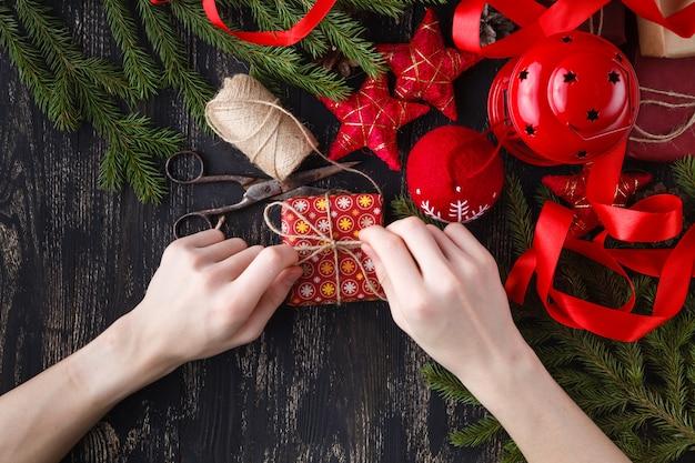 Kreatives hobby. hände wickeln weihnachtsfeiertag handgemachtes geschenk in bastelpapier mit schnurband